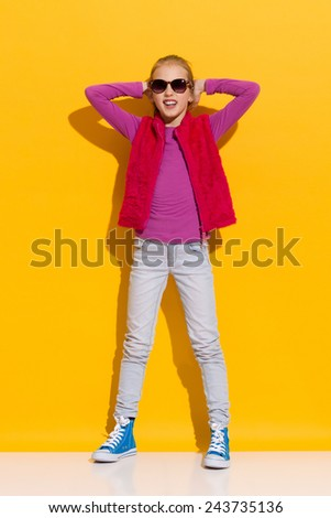 Relaxed girl. Young blond girl standing and holding hands behind head. Full length studio shot on yellow background. - stock photo