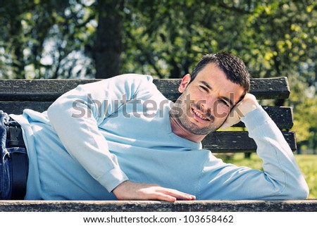 relaxed handsome man on a bench in a park - stock photo