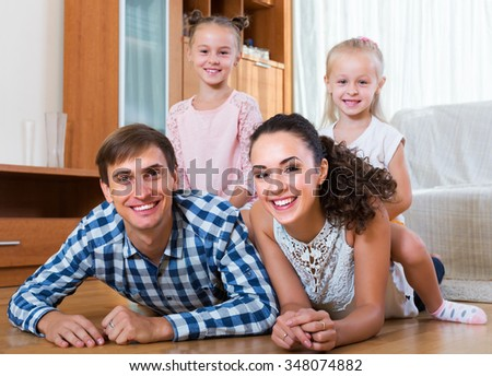Relaxed happy family of four posing in livingroom