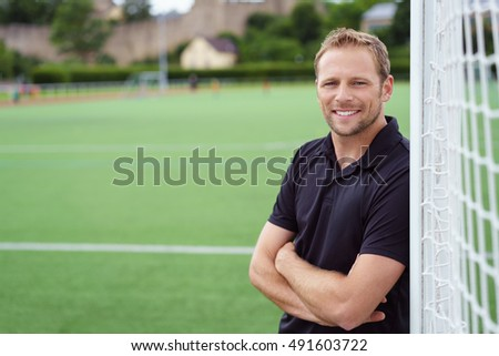 Relaxed happy football coach leaning on the goal posts with folded arms grinning at the camera, close up with copy space