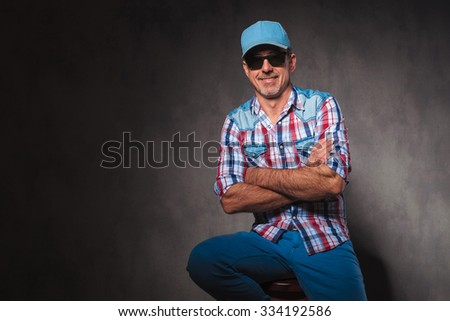 relaxed happy old casual man sitting with hands crossed in studio, wearing trucker hat - stock photo