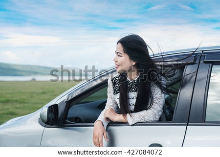 Relaxed happy woman on summer road trip travel vacation leaning out car window on blue sky background. - stock photo