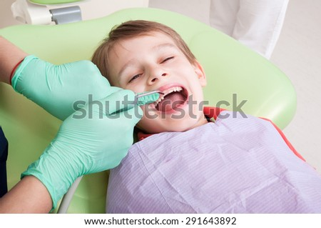 Relaxed kid in dentist chair ready for checkup procedure - stock photo