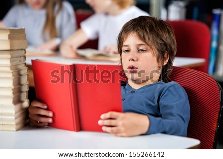 Relaxed little schoolboy reading book while sitting at table in library - stock photo