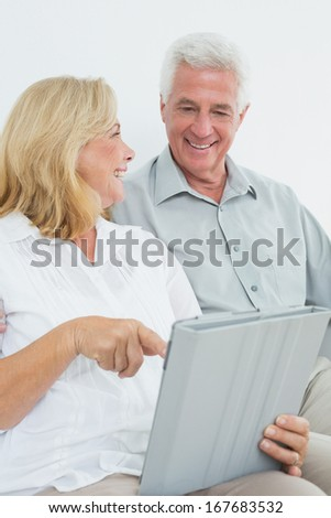 Relaxed loving senior couple using digital tablet on sofa in a house