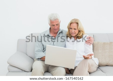 Relaxed loving senior couple using laptop on sofa in a house