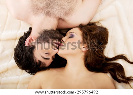 Relaxed loving young couple kissing in bed.