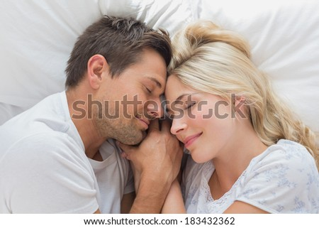 Relaxed loving young couple lying in bed with eyes closed at home - stock photo