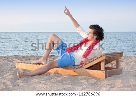 Relaxed male  on wooden sand bed calling others at sea side - stock photo