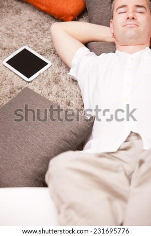 relaxed man having finally his time off in his living room and his beloved  couch - stock photo