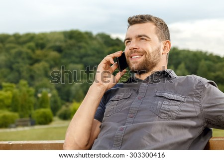 Relaxed man in park talking on mobile phone