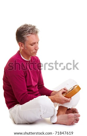 Relaxed man playing on a version of the African instrument Kalimba - stock photo