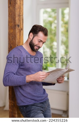 Relaxed man standing reading a newspaper while leaning against an old wooden door jamb at home smiling as he reads the news - stock photo