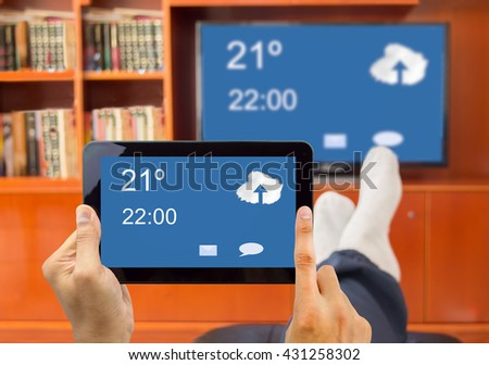 relaxed man with tablet connected to a tv through wireless connection in networking - stock photo