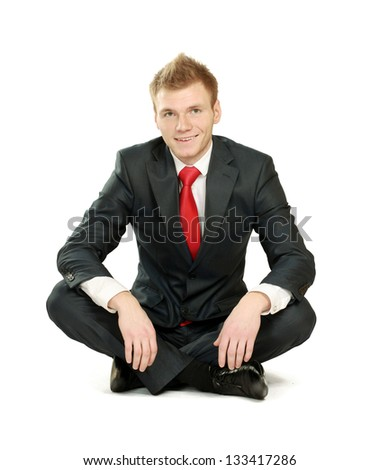 Relaxed mature business man sitting on the floor, isolated on white background