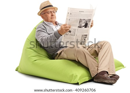 Relaxed mature man reading a newspaper seated on a green beanbag isolated on white background - stock photo