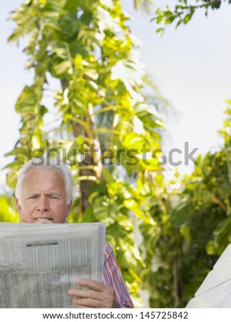 Relaxed mature man reading newspaper against plants outdoors - stock photo