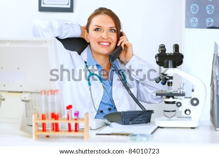 Relaxed medical doctor woman sitting at office table and talking on phone - stock photo