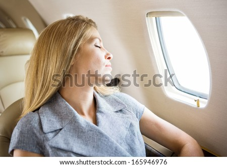 Relaxed mid adult businesswoman sleeping in private jet - stock photo