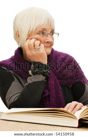 Relaxed old woman looking at something interesting while reading a book - stock photo
