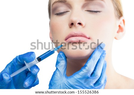 Relaxed pretty model on white background having an injection on the lips
