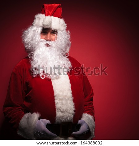 relaxed santa claus is standing with his hands on belt and smiles to the camera,  on red background