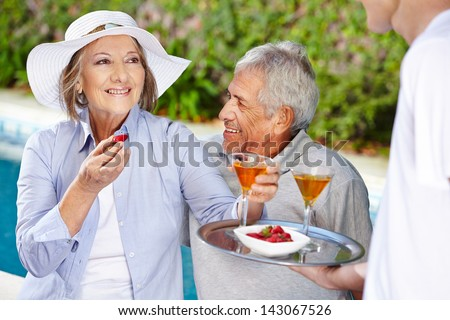 Relaxed senior couple in holiday at the pool drinking cocktails