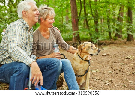 Relaxed senior couple sitting with dog in a forest during a hiking trip - stock photo