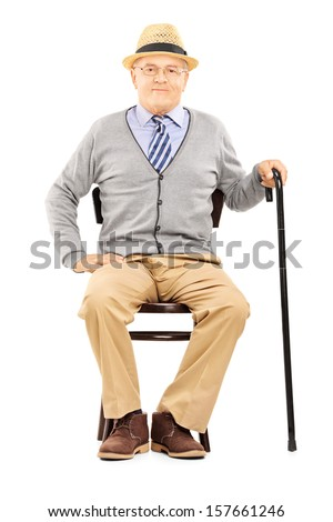 Relaxed senior man sitting on a wooden chair and looking at camera isolated on white background - stock photo