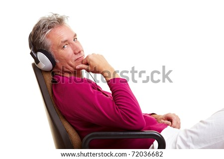 Relaxed senior man sitting on office chair and listening to music with headphones - stock photo