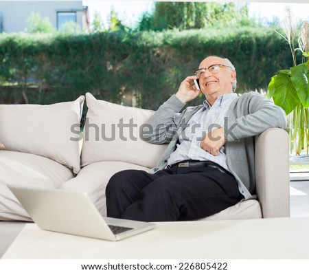 Relaxed senior man using mobile phone while sitting on couch at nursing home porch - stock photo
