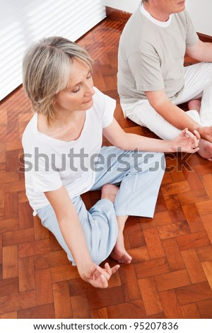 Relaxed senior people meditating in yoga class in gym - stock photo