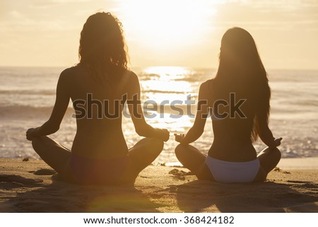 Relaxed sexy young brunette women or girls wearing bikini sitting on a deserted tropical beach at sunset or sunrise - stock photo