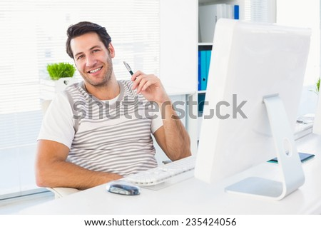 Relaxed smiling man with computer in a bright office - stock photo