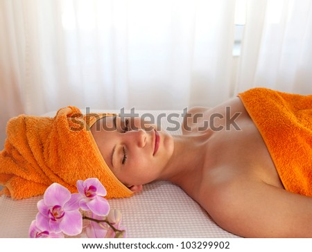Relaxed smiling woman with a peaceful expression lying on a table enjoying a spa treatment in orange towels and accessories