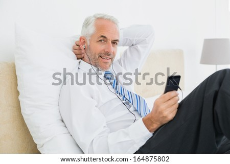 Relaxed well dressed man listening music with his phone in bed at home