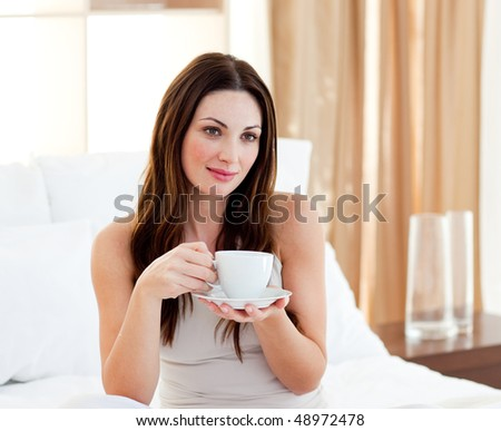 Relaxed woman drinking coffee sitting on bed at home