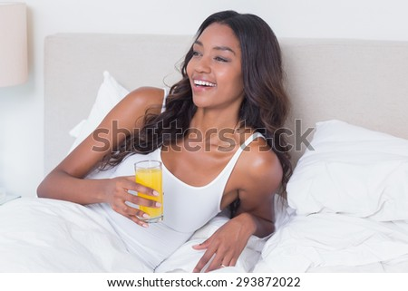 Relaxed woman drinking orange juice at home in bedroom - stock photo