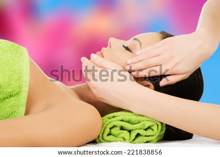 Relaxed woman enjoy receiving face massage at spa saloon - stock photo