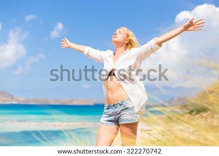 Relaxed woman enjoying freedom and life an a beautiful sandy beach.  Young lady raising arms, feeling free, relaxed and happy. Concept of freedom, happiness, enjoyment and well being. - stock photo