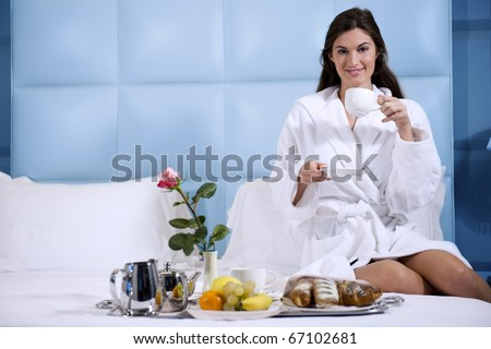 Relaxed Woman Having Breakfast in Bed, home or hotel room - stock photo