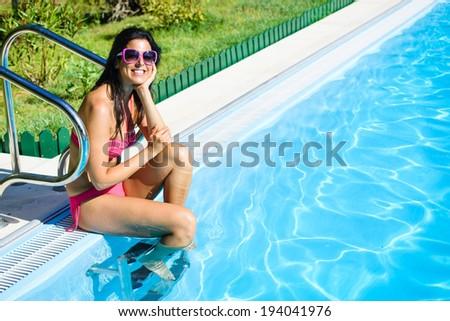Relaxed woman in bikini enjoying summer vacation leisure at swimming pool. - stock photo