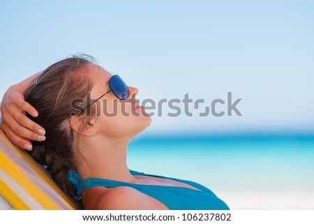 Relaxed woman laying on beach - stock photo