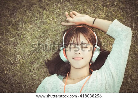 Relaxed woman listening to the music with headphones lying on the grass , vintage tone - stock photo