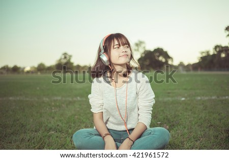 Relaxed woman listening to the music with headphones  on the grass , vintage tone - stock photo