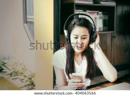 relaxed woman listening to the music with headphones,young woman with headset and listening to music while playing with her smartphone - stock photo