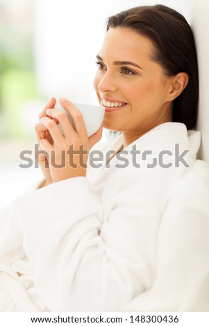 relaxed woman on bed drinking morning coffee and daydreaming - stock photo
