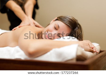 Relaxed woman receiving a massage in a spa  - stock photo
