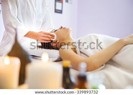 Relaxed woman with a deep cleansing nourishing face mask applied to her face. Spa treatment - stock photo