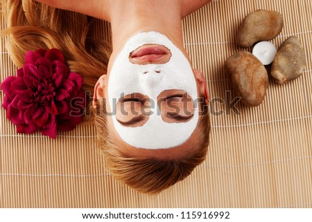 Relaxed woman with a face mask lying on her back on a mat in a spa with her eyes closed - stock photo